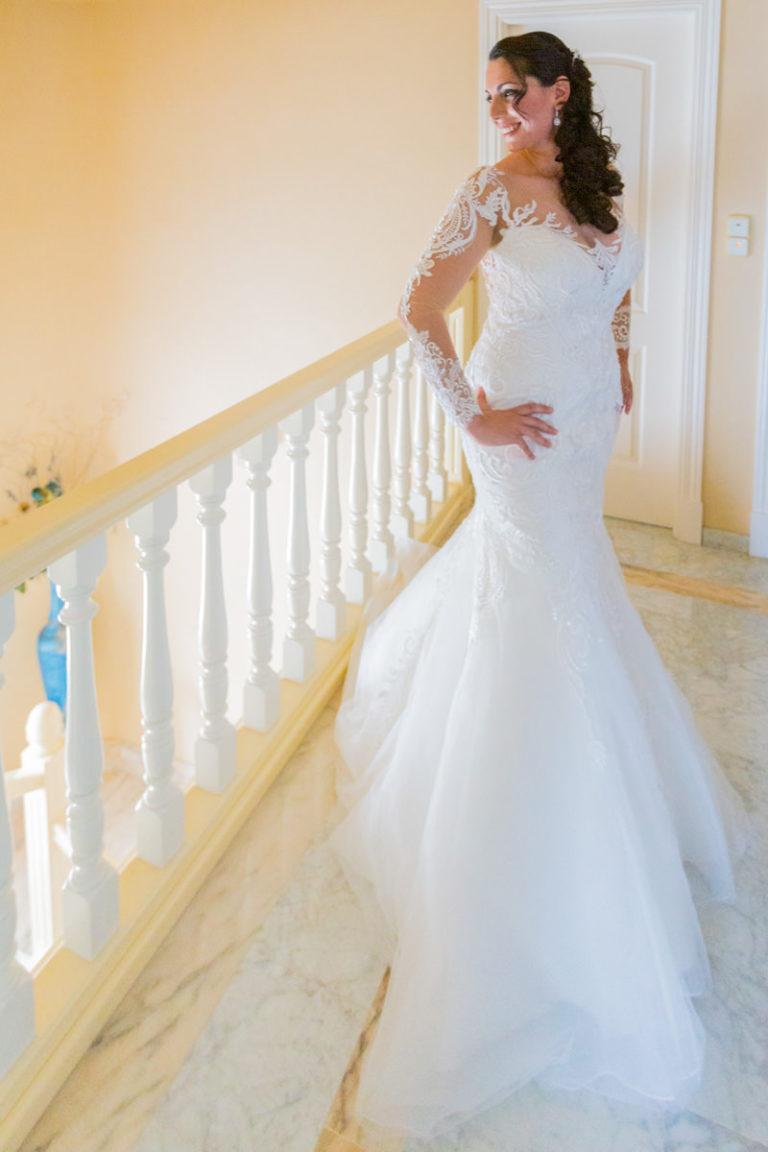 Preciosa novia con vestido blanco en las escaleras de la Iglesia de Madrid.