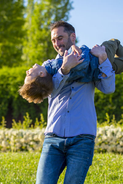El novio juega en un prado verde con su sobrino rubio antes de su bodas en Madrid.