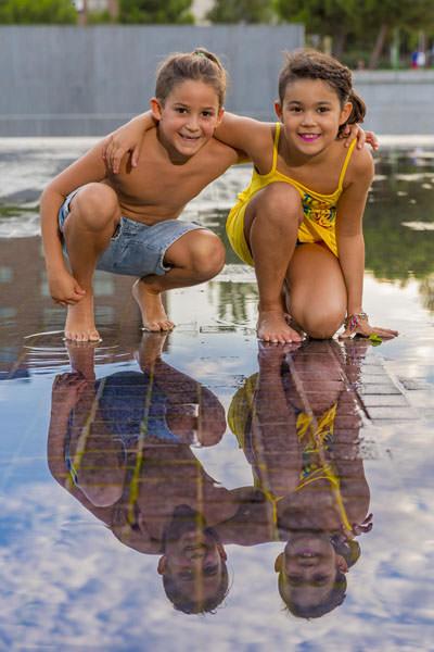 Preciosa pareja de niños jugando en la piscina del hotel de madrid donde se celebra la boda.